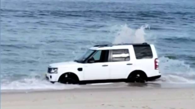 A stranded Land Rover SUV is hit by waves on a beach in the US.