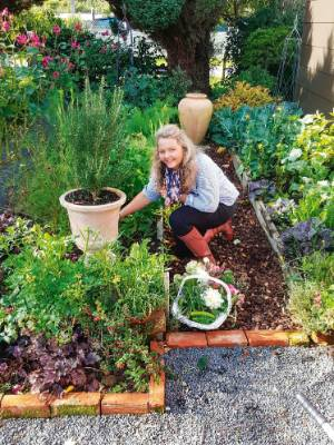 Sally in her edible garden. The pathway is made from peach stones.