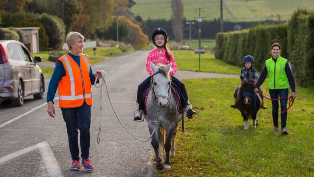 Keeping an eye out for traffic as they ride roadside are, from left, Linda Pullar, Sophie Coleman, 7, Noah Coleman, 6, ...