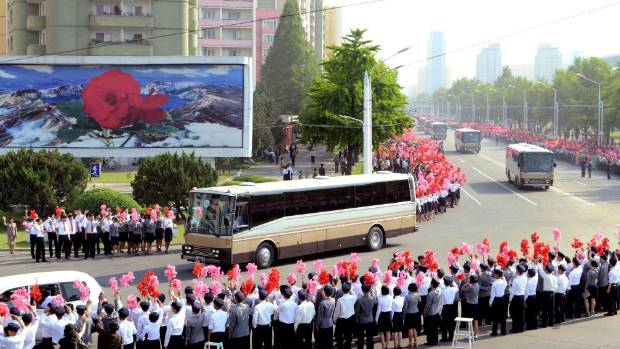 Members of the public cheer as North Korean missile developers go by.