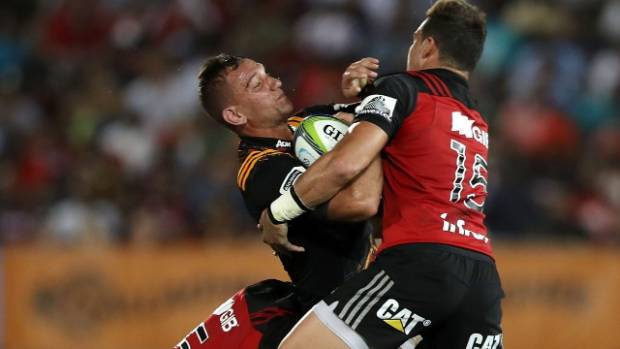 Aaron Cruden of the Chiefs is tackled by Sam Whitelock and David Kaetau Havili of the Crusaders during the Super Rugby ...