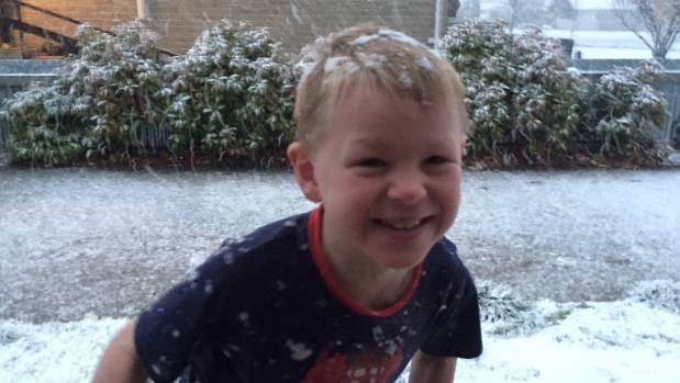 Travis Chamberlain, 6, can't wait to get a jacket and runs out in his pyjamas to see the snow falling in Cromwell on ...