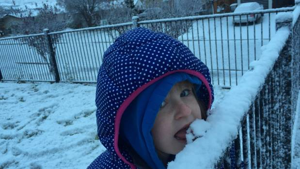 Morgan Chamberlain, 4, tastes some snow in Cromwell.