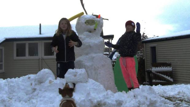 Ella Stuart, 9, Grace Stuart, 7, and Charlie the neighbour's  dog make a snowman (dad may have helped).