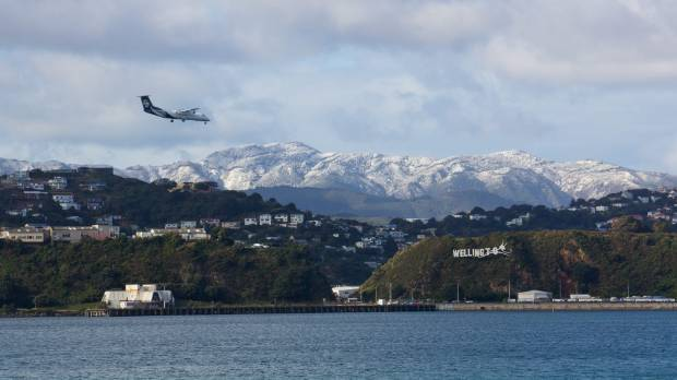Snow on the Orongorongos, with an Air New Zealand plane flying in over Wellington's Evan's Bay.