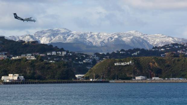 Snow on the Orongorongos, with an Air New Zealand plane flying in over Wellington's Evan's Bay on Saturday.