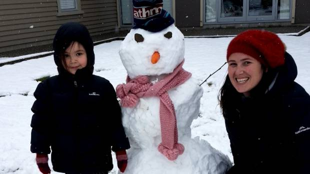 Tyla, left, and Steph Scherger save a pretty pink scarf for their snowman/snowlady in Arrowtown.