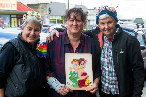 Topp Twins, Lynda (left), Jools (right) with Pania Molloy holding the original painting she created that was used as the ...