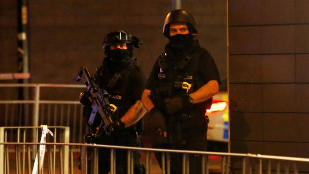 Armed police officers stand next to a police cordon outside the Manchester Arena.