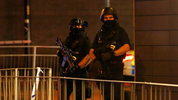 Armed police officers stand outside the arena.