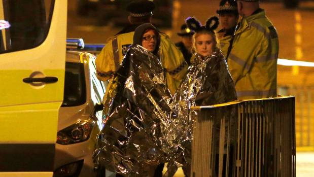 Two concertgoers are given thermal blankets after the blast.