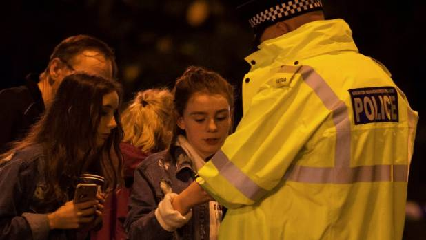 Police assist fans who fled from the deadly concert blast in Manchester.