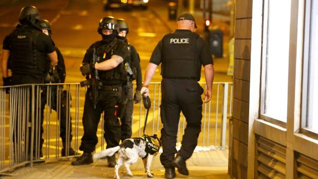 Police walk around the Manchester Arena with a sniffer dog.