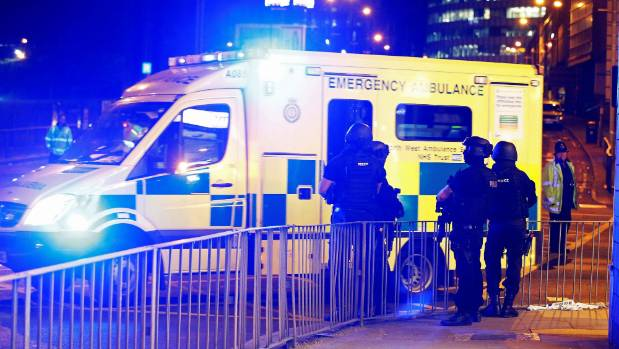 An ambulance pulls away from the Manchester Arena as armed police officers watch on.