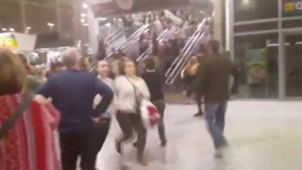 People running down stairs as they attempt to exit the Manchester Arena.