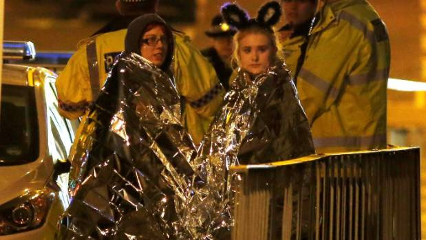 Two women wrapped in thermal blankets stand near the Manchester Arena.