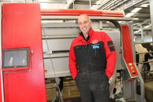 Revolution Dairies director David Johnston with one of his Lely A4 robots while it milks a cow on the Wreys Bush farm.
