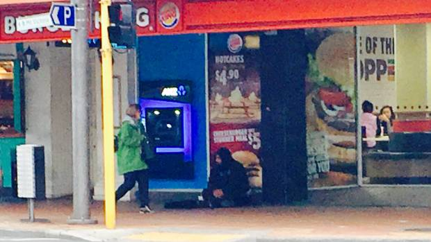 A beggar beside another ATM, in Courtenay Place, on Tuesday.