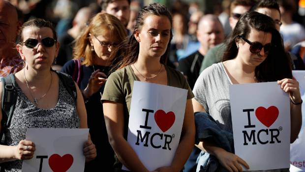 Women wait to take part in a vigil for the victims of an attack on concert goers at Manchester Arena.