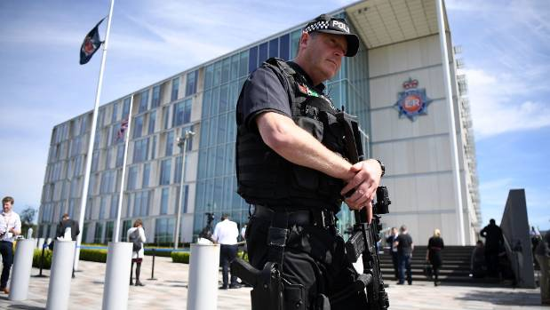 Armed police guard Greater Manchester Police station as a flag flies at half-mast in the aftermath of Monday night's ...