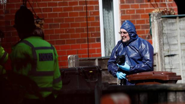 Police investigators work at residential property in south Manchester, England.