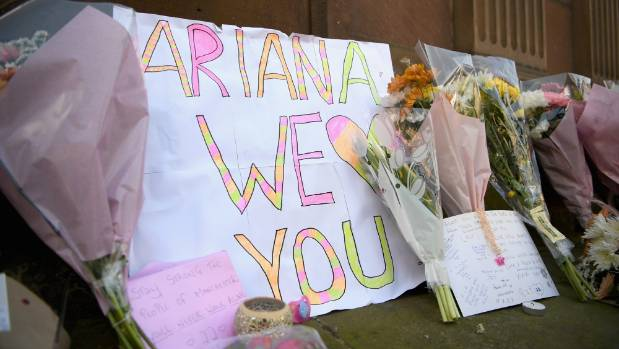 A sign saying 'Ariana we heart you' is displayed among flowers left in St Ann Square in Manchester, England.