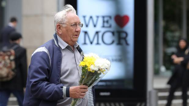 "A man carrying a floral tribute walks past a ""We Love MCR"" sign which have been put up all around the city after Monday ..."