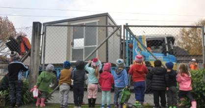 Children line the fence during the surprise delivery of Marlborough Street Childcare Centre's new resource room.