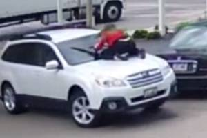 With the thief trying drive away in her car, Melissa Marian clings to the bonnet of her car at a service station in ...