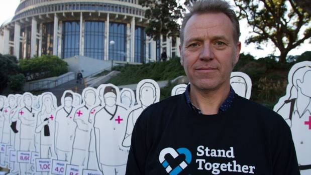 Andy Colwell stands in front of 200 life-sized cut-outs of health workers, said to represent 20,000 health workers ...