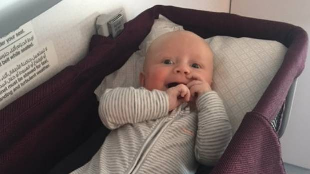 Happy bubs in his bassinet on the plane three months old