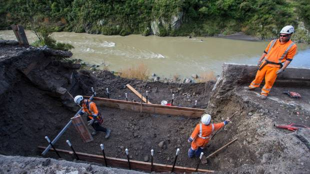 Higgins contractors work on a fallen section of road at the Manawatu Gorge.