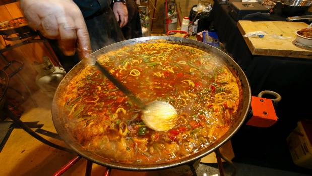 Paella is a Spanish dish of rice with chicken or seafood,cooked and served in a large shallow pan.