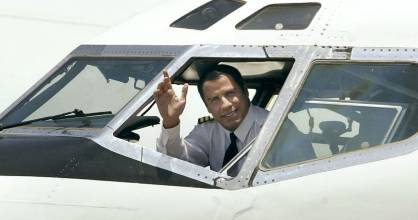 John Travolta sits in the cockpit of his Boeing 707 airline in June 2002.