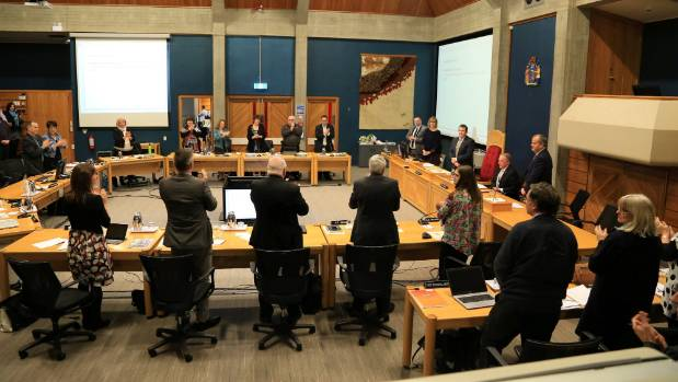 Palmerston North City councillors stand in honour of retiring chief executive Paddy Clifford.