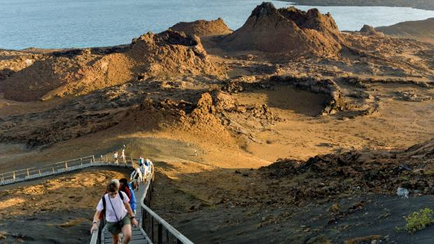 Tourists climbing the peak of the volcanic landscape of Bartolome Island.