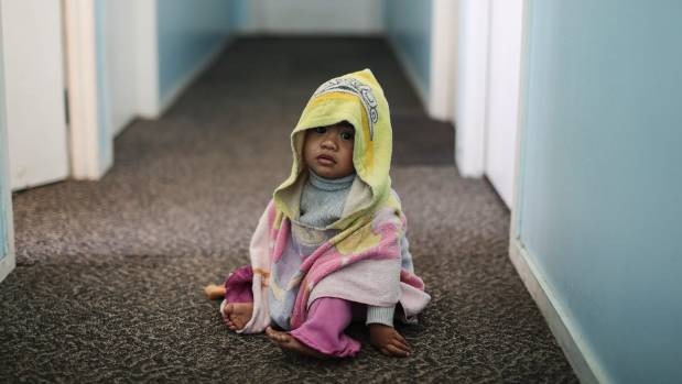 Julia Alatina (18 months) at the boarding house where she lives with her family.