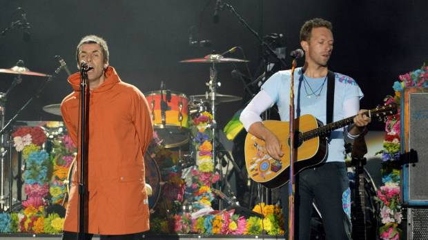 Liam Gallagher and Chris Martin perform on stage on June 4, 2017 in Manchester.