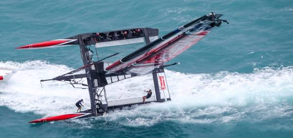 Team NZ sailors hold on as their craft is righted after a capsize during the America's Cup challenger series semifinals.