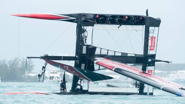 Emirates Team New Zealand crew members wait for rescue after capsizing on the Great Sound in Bermuda.