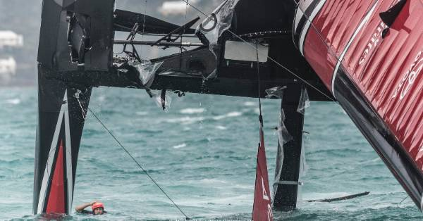 A Team New Zealand crewman in the water after their disastrous pitch-pole.