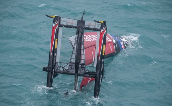 Team New Zealand lies stricken in the water after capsizing.