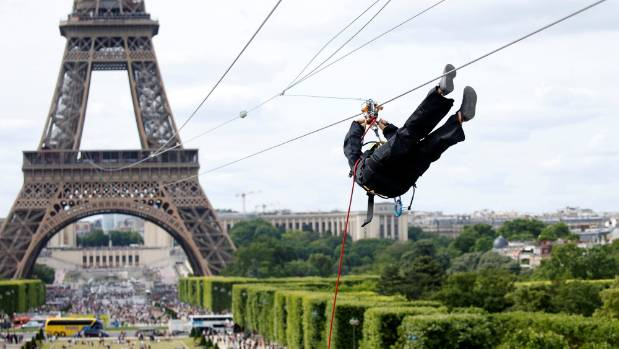 Daredevils zip-line off the Eiffel Tower