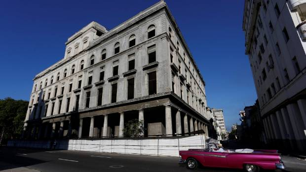 A vintage car drives past a historic building undergoing renovation in Havana