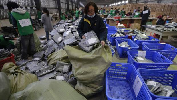 Employees sort packages at a hub of China Post's express delivery service in Wuhan, Hubei province.