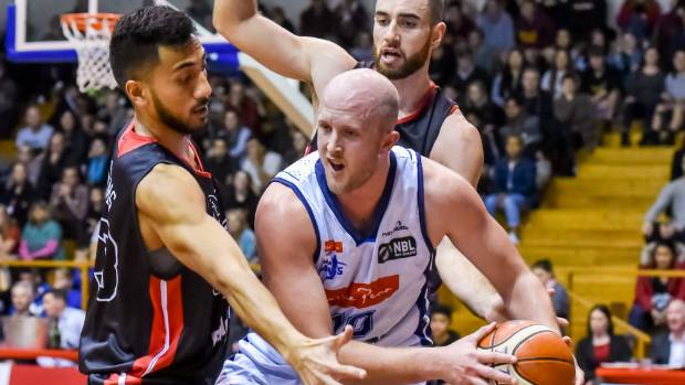 Nelson Giants captain Sam Dempster looks to make a pass under pressure from Canterbury Rams players Ben Williams and ...