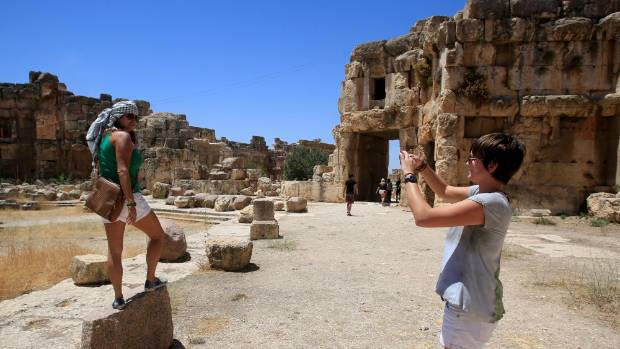 Tourists take pictures during their visit to the Roman ruins of the Baalbek Temples, in eastern Lebanon.