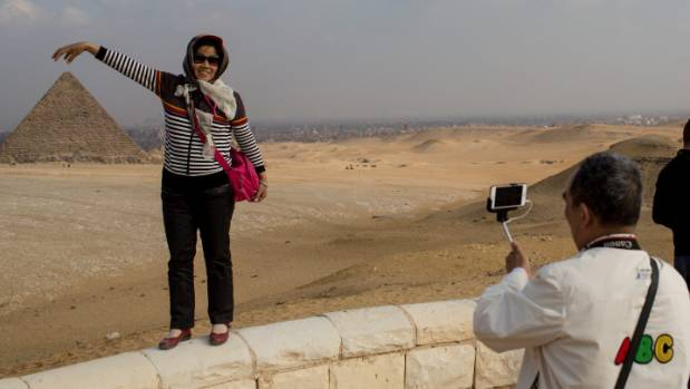 Tourists take photographs in front of Egypt's famous Giza Pyramids. The entire country is under threat from ISIS.
