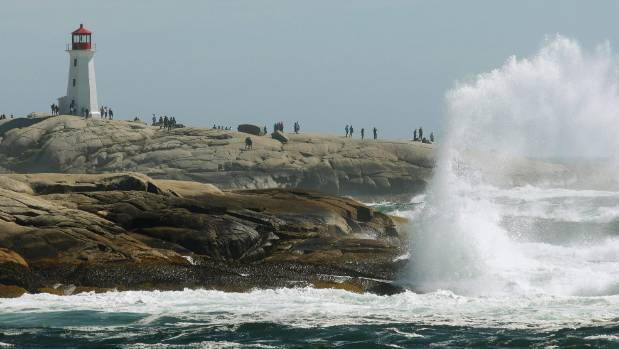 Waves crash over the rocks near the lighthouse at Peggy's Cove in Nova Scotia.