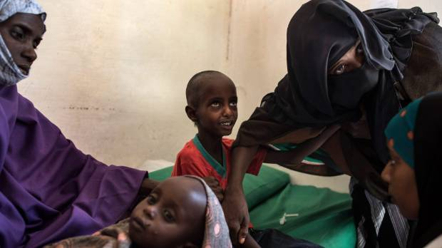 Abdullahi Mohamud, 5, cries next to his mother Sahro Mohamed Mumin, 30, and brother, Abdulrahman Mahamud, 2, as a nurse ...